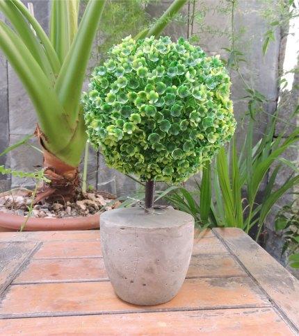 Arbol artificial con base de cemento, color verde. Foto completa.