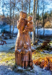 A woodcarving depicting a young woman with a babe in arms and young child holding her skirt