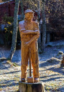 A woodcarving of a working man rolling up his sleeves