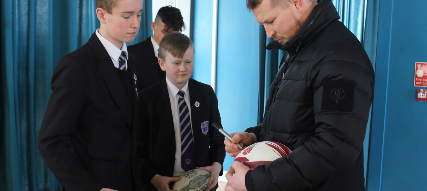 Former England Rugby Captain Dylan Hartley signing a rugby ball at Gainsborough Academy