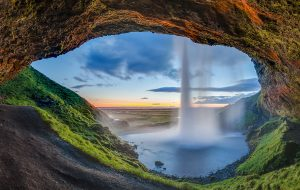 Sunset view from the back of the Seljalandsfoss waterfall, Suðurland, Iceland. The waterfall of the river Seljalandsá drops 60 metres (200 ft) over the cliffs of the former coastline - IRA