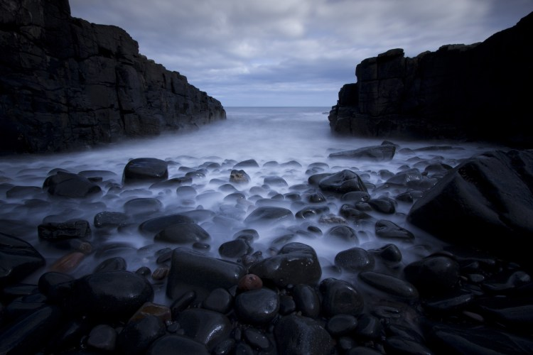 rocks pebbles sea long exposure ocean beach pooled income funds