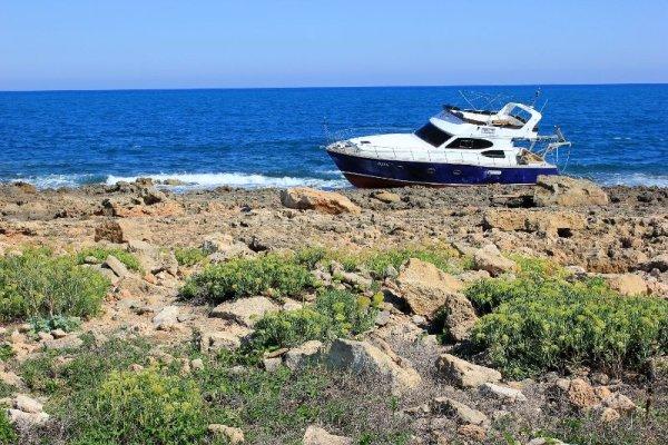 Costa rocciosa con uno yacht costa nella Riserva di Vendicari