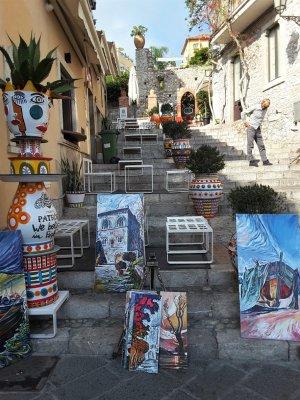 Ceramiche e quadri in vendita su una scalinata di Taormina