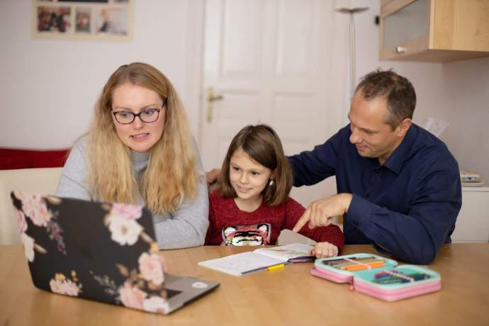 A mother and a father homeschooling their daughter.