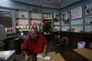 Un empleado permanece a la espera de clientes en el interior de una bodega estatal, que vende productos racionados, precariamente provisto, en un barrio de La Habana. Este tipo de negocios forman parte de un modelo en revisión en Cuba.