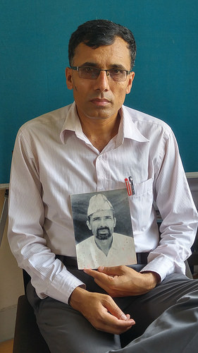 Suman Adhikari, chairperson of Nepal's Conflict Victims Common Platform, holding a photo of his father. Credit: Marty Logan/IPS