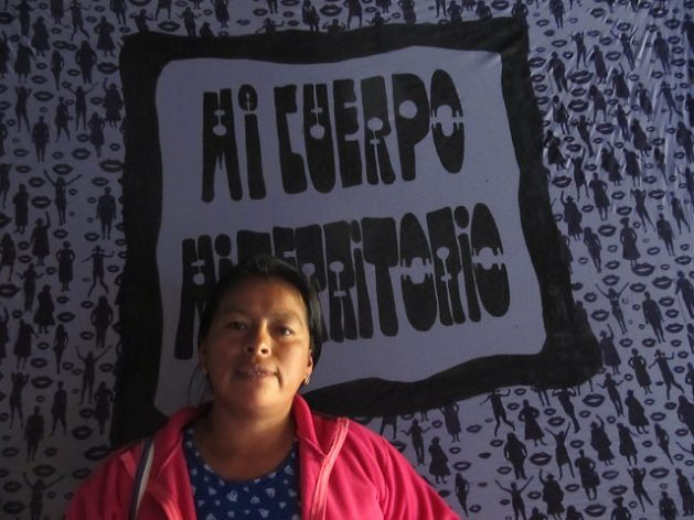 "Fanny Kaekat, indigenous leader of the Shuar Arutam people, has spent her life defending the territories of indigenous communities in southeastern Ecuador from the threat of mining. She poses at the 14th Latin American Feminist Meeting, in Montevideo, in front of a poster that reads: ""my body, my territory"", a slogan of women human rights defenders. Credit: Mariela Jara / IPS"