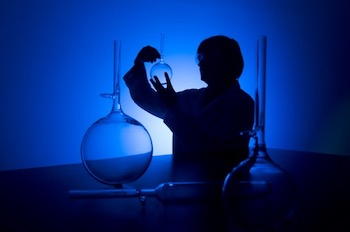Silhouette of a female researcher carrying out research in a chemistry lab