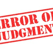 ERROR OF JUDGMENT red Rubber Stamp over a white background.