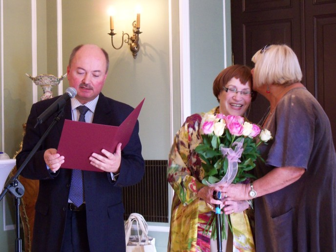 The 'Merit of Good' from the country of Poland is given to Renata Zajdman by the special assistant to the Foreign Minister in a ceremony at the Foreign Ministry Palace