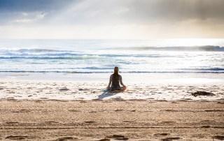 Femme pratiquant le yoga à la plage