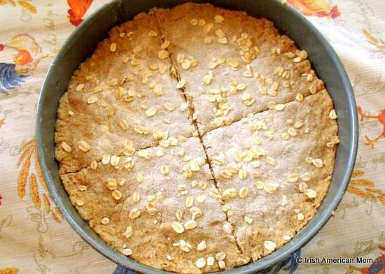 Brown bread dough marked with a cross in a baking tin prior to going in the oven