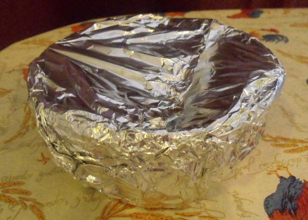 Plum pudding in bowl with aluminum foil