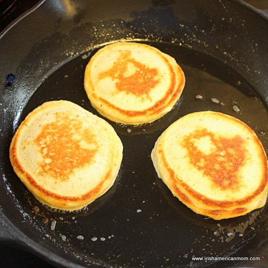 Three drop scones cooking on a pan