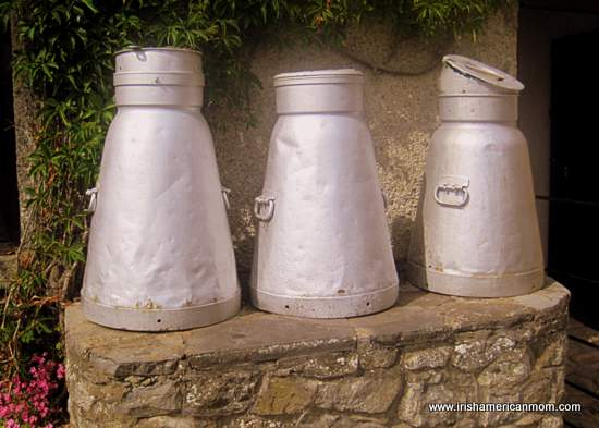 Three milk churns on a milk stand