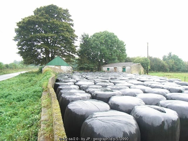 Silage bales by farm sheds in Ireland