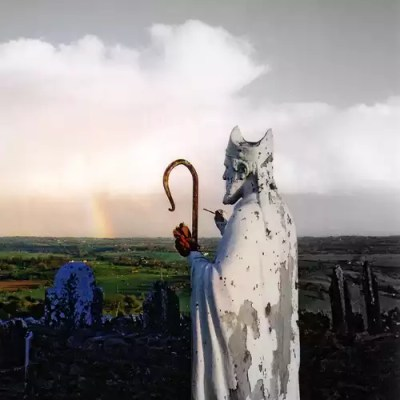 Statue of St Patrick overlooking green fields and a rainbow