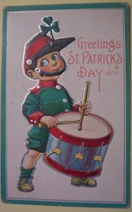 A card bearing a drawing of a drummer boy, dressed in green with red trim. Message: Greetings. St Patrick's Day.