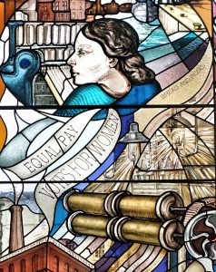 "Stained class window depicting mill machinery, a woman in profile and ribbons saying ""equal pay"", ""votes for women"", ""roses and bread"" (slogans of suffrage and social justice movements)"