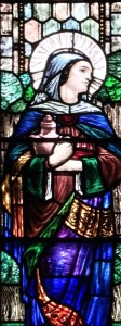 Stained glass window depicting a woman holding a jar. Her head is framed with a halo bearing the name: Mary of Bethany
