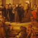 Luther stands in front of the church doors as his theses are nailed to it. A watching crowd has mixed reactions: friars leave angrily, a group around Luther seem supportive, one well-dressed man cheers, most look on in curiosity.