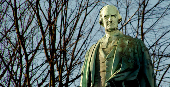 Statue of Henry Cooke against bare tree branches