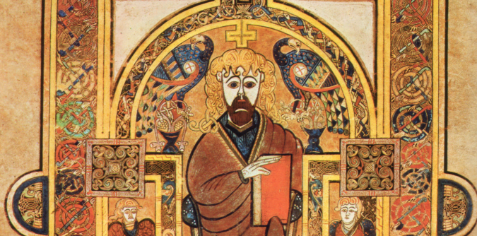 A bearded Christ with long hair sits, a red book in his left hand, with eagles either side of his head, a cross over him, surrounded by interlaced borders