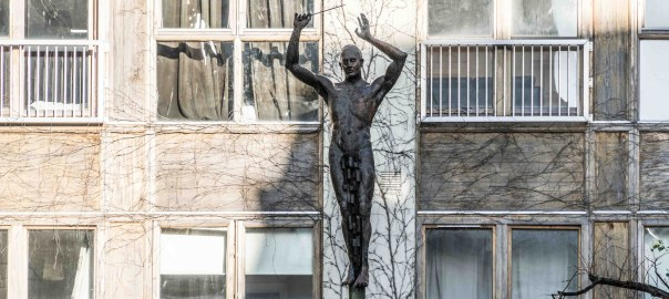 A bronze statue of a naked male figure raising his arms as if to conduct a choir, baton in hand. He is posed against a background of windows, and walls covered with creeper stems