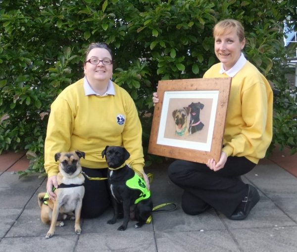 Susan from Dublin, who won our 2013 Annual Draw  is presented with a painting of her dogs Bart and Lois by the artist Claire  (right).