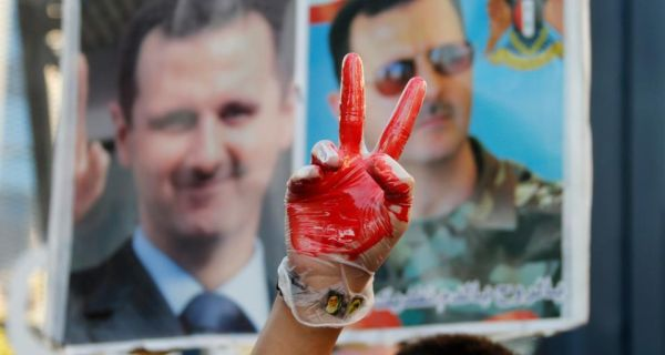 A supporter of Syria's president Bashar al-Assad gestures while wearing a glove with fake blood in front of pictures of Assad during a sit-in near the US embassy in Awkar, north of Beirut, against potential US strikes on Syria. Photograph:  Mohamed Azakir/Reuters