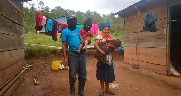 Marcelo and Maria, Michael McCaughan's hosts at the Zapatista village of Moises Gandhi, with their youngest two children, outside their home. The ski masks are worn as the Zapatistas still remain officially outside the law. Photograph: Sergio Chua