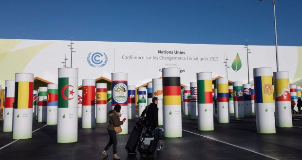 Delegates walk among poles bearing national flags at entrance to the COP21 world climate change conference. Photograph: EPA/Ian Langsdon