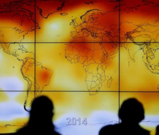 Participants Are Seen In Silhouette As They Look At A Screen Showing A World Map With