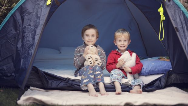 Two young brothers ready for bed and super excited about camping out in the garden in summer.