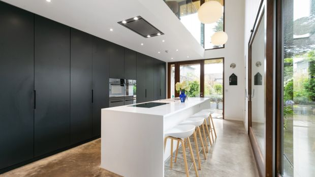 Kitchen – with wall of black units and white Corian island – of 8 Crosthwaite Park East