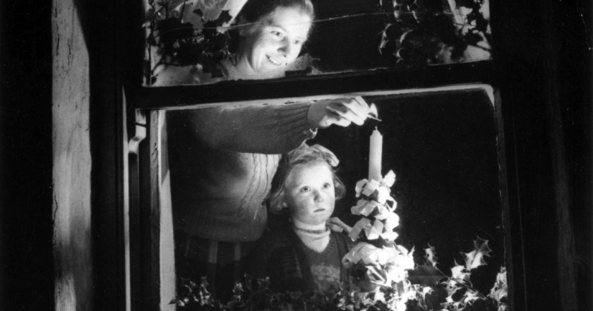 """A girl watches her mother light a candle in the window of their cottage in 1995. """"Of all the rediscovered traditions we add to the festivities, it is the candle in the window that I like best."""" Photograph: Three Lions/Getty Images"""