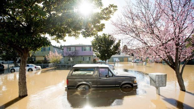 A Ford Bronco rests in floodwaters in February 2017, in the Rock Springs area of San Jose, California. The IPCC report says climate change is bringing more intense rainfall and associated flooding. Photograph: Getty Images