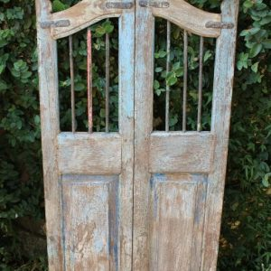 Garden gate with worn paint and iron bars