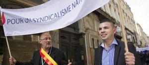 Thierry Gourlot, FN, and Fabien Engelmann, FN mayor of Hayange, holding a banner reading: 'For national syndicalism'