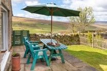 Table and chairs with parasol in back garden.