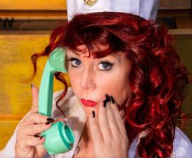 Joy Club im Test - Bild von Krankenschwester mit Telefon und roten Haaren die schaut