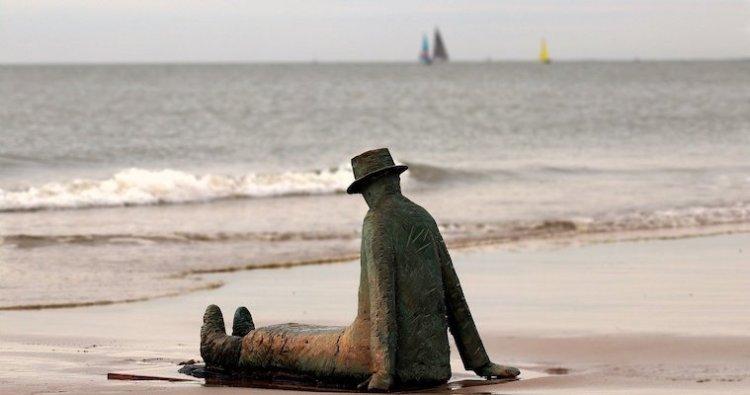 Un statue d'un homme assis sur la plage et regardant au loin.