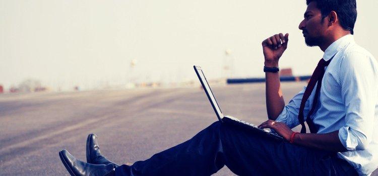 Un homme travaille et réfléchit, assis sur le bitume dans la chaleur