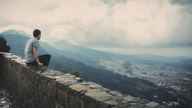 Un homme, assis sur un muret de pierre, contemple les montagnes et une ville au loin.