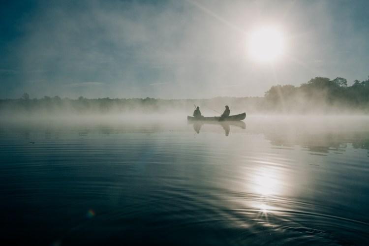Deux pêcheurs en chaloupe dans le soleil qui se lève: un magnifique loisir en forêt.