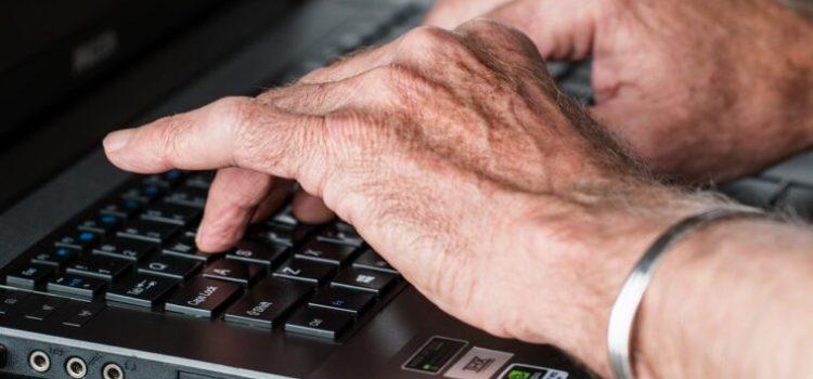 Les mains d'un homme qui tape à l'ordinateur évoquent un gestionnaire en télétravail
