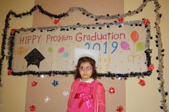 Girl in front of graduation sign