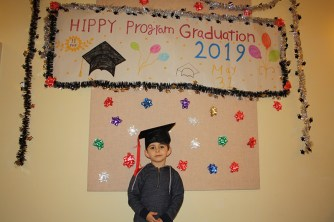 Little boy in front of graduation sign