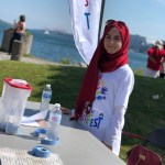 Rayan Shehab standing at a table while volunteering with Nova Multifest